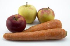 Wortelen en appelen op witte achtergrond worden ge?soleerd die stock foto's