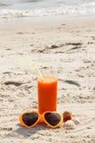Wortelsap en zonnebril bij strand, concept vitamine A en mooie, duurzame tan stock foto