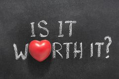 Is it worth heart. Is it worth it question handwritten on blackboard with heart symbol instead of O stock image