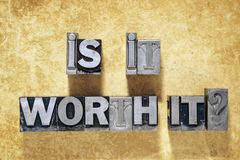 Is it worth it. Question phrase made from metallic letterpress type on grunge cardboard background stock image