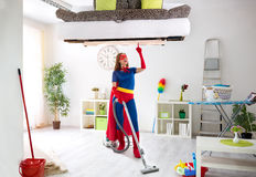 Worth super hero woman in costume use vacuum cleaner. Hygiene time stock photo