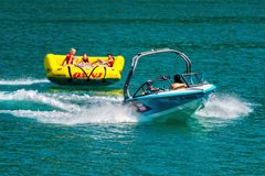 WORTHERSEE, AUSTRIA - AUGUST 08, 2018: Happy young people, on inflatable attractions, drive behind a motorboat on the lake. WORTHERSEE, AUSTRIA - AUGUST 08 royalty free stock image