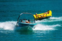 WORTHERSEE, AUSTRIA - AUGUST 08, 2018:  Happy young people, on inflatable attractions, drive behind a motorboat on the lake. WORTHERSEE, AUSTRIA - AUGUST 08 stock photos