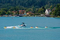 WORTHERSEE, AUSTRIA - AUGUST 08, 2018:  Happy young people, on inflatable attractions, drive behind a motorboat on the lake. WORTHERSEE, AUSTRIA - AUGUST 08 royalty free stock photography