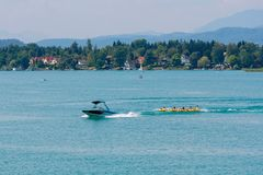 WORTHERSEE, AUSTRIA - AUGUST 08, 2018:  Happy young people, on inflatable attractions, drive behind a motorboat on the lake. WORTHERSEE, AUSTRIA - AUGUST 08 royalty free stock photo