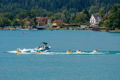 WORTHERSEE, AUSTRIA - AUGUST 08, 2018:  Happy young people, on inflatable attractions, drive behind a motorboat on the lake. WORTHERSEE, AUSTRIA - AUGUST 08 stock image