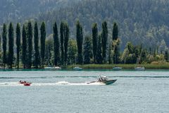 WORTHERSEE, AUSTRIA - AUGUST 08, 2018:  Happy young people, on inflatable attractions, drive behind a motorboat on the lake. WORTHERSEE, AUSTRIA - AUGUST 08 royalty free stock photos