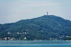 WORTHERSEE, OOSTENRIJK - AUGUSTUS 08, 2018: Wortherseemening bij turkoois water van meer in de zomerbergen in afstand toeristen royalty-vrije stock foto's