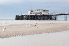 Worthing beach and pier in a cloudy day, low tide, England. Royalty Free Stock Images