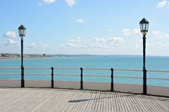Worthing pier and seafront. England. Beach and seafront at Worthing, West Sussex, England. Viewed from end of pier. With lamps and railings Royalty Free Stock Photography