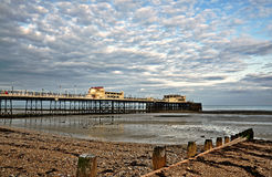 Worthing pier and shingle beach. View of the Grade 2 listed Victorian pier at Worthing, West Sussex, built in 1862, with shingle beach and  wooden groynes Stock Photos