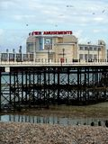 Worthing Pier, Sussex, England. A view of Worthing Pier at dusk with low tide, blue sky, shingle beach, seagulls Stock Image