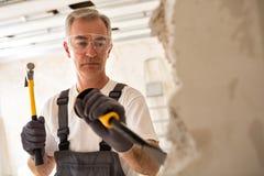 Worthy senior man working with hammer and tool while demolish wa. Ll,close up stock photos