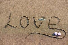 Wortliebe auf Sandhintergrund Stockbild