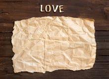 Wortliebe und -papier auf altem Holz Lizenzfreie Stockfotos