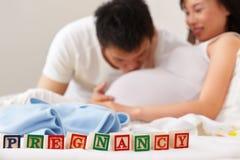 Wortschwangerschaft vor glücklichen Paaren Stockfoto