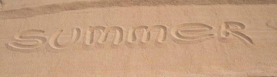 Wortsommer wird auf eine sandige Oberfläche geschrieben Stockbilder