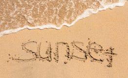 Wortsonnenuntergang geschrieben in den Sand Lizenzfreie Stockfotos