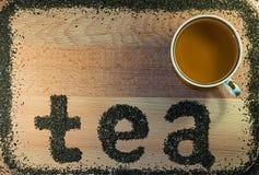 Worttee wird auf einem schwarzen Tee des hellbraunen Blattes des hölzernen Brettes kleinen ausgebreitet Stockfotografie