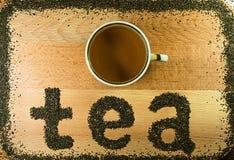 Worttee wird auf einem schwarzen Tee des hellbraunen Blattes des hölzernen Brettes kleinen ausgebreitet Lizenzfreies Stockfoto