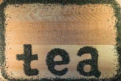 Worttee wird auf einem schwarzen Tee des hellbraunen Blattes des hölzernen Brettes kleinen ausgebreitet Lizenzfreies Stockbild