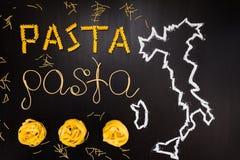 Wortteigwaren gemacht von gekochten Spaghettis und trockene Teigwaren auf dem schwarzen Hintergrund mit dem Rahmen des Landes Ita Stockbild