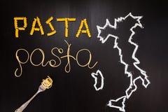 Wortteigwaren gemacht von gekochten Spaghettis und trockene Teigwaren auf dem schwarzen Hintergrund mit dem Rahmen des Landes Ita Stockfotos