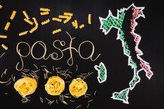 Wortteigwaren gemacht von gekochten Spaghettis und trockene Teigwaren auf dem schwarzen Hintergrund mit Rahmen des Landes Italien Lizenzfreie Stockfotografie