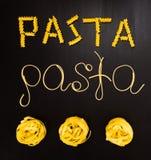Wortteigwaren gemacht von gekochten Spaghettis und trockene Teigwaren auf dem schwarzen Hintergrund mit dem Rahmen des Landes Ita Stockfotografie