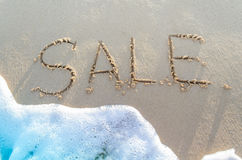 Wortverkauf handgeschrieben im Sand Stockfotografie