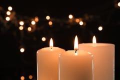 Wosk świeczki pali przeciw zamazanym światłom obraz stock