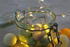 Wosk wiśnie w słoju szkle z DOWODZONYMI światłami i Bożenarodzeniowymi piłkami Fotografia Royalty Free