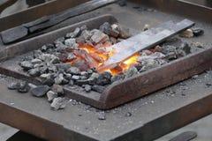 Wotk de forgeron avec le marteau et le fer chaud Photographie stock