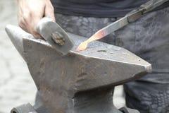 Wotk de forgeron avec le marteau et le fer chaud Photos stock