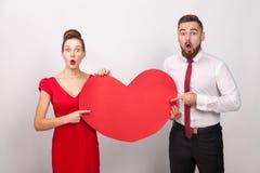 Wouah ! Grand amour Couples demandés dirigeant des doigts au rouge entendu Photo stock