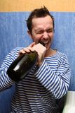 When it would be desirable to get drunk. Portrait of the unshaven man, opening teeth a wine bottle Stock Photography