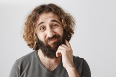 It would be problematic. Portrait of hesitating unsure eastern man scratching beard and lifting eyebrows with doubtful. Expression, being unaware if he can make royalty free stock images