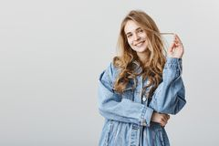 Would you like to continue our talk in bar. Portrait of sensual charming woman in stylish outfit playing with hair. Strand and smiling broadly, flirting or Royalty Free Stock Images