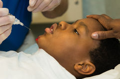 Wound Care. An African American boy gets an injection of local anesthesia into a wound Royalty Free Stock Photography