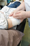 Wounded. Nurse bandaging patient with gauze Stock Photo
