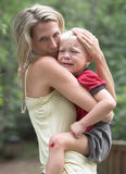 Wounded boy and his mother. Little boy injured his knees Stock Photography