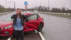 A woman was in an accident on the road in the rain, she is injured and scared. The wounded girl stands near the broken car in the rain, she is wounded and holds stock video