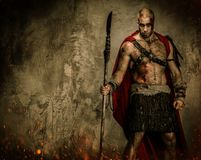 Wounded gladiator with spear. Wounded gladiator in red coat holding spear stock photos