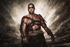 Wounded gladiator with sword. Against stormy sky stock images