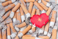 Wounded heart on cigarette bulls Stock Photo