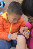 Wounded kid. Chinese kid fallen down from bicycle and leg wounded, mom caring him Royalty Free Stock Photos