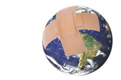 Wounded Planet Earth Isolated. Isolated image a wounded planet earth with first aid plasters Royalty Free Stock Images