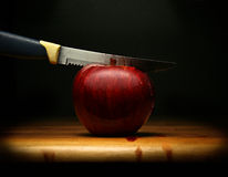 Wounded Red Apple. A knife cutting a red apple with blood flowing on, with a dark background Stock Images