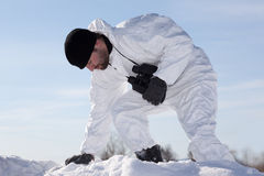 Wounded soldier in white camouflage sneaking through the mountai Stock Photo