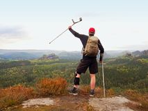 Wounded tourist with crutch above head achieved mountain peak. Hiker with  knee brace feature. Royalty Free Stock Photo